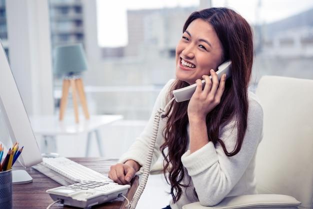 Lächelnde asiatin bei einem telefonanruf unter verwendung des computers im büro