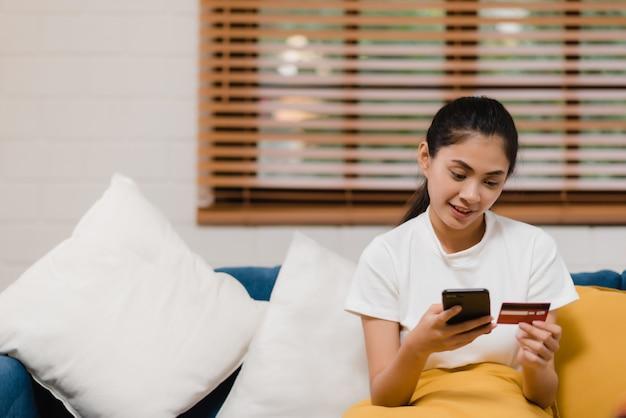Lächelnde asiatin der junge, die den smartphone kauft das on-line-einkaufen verwendet