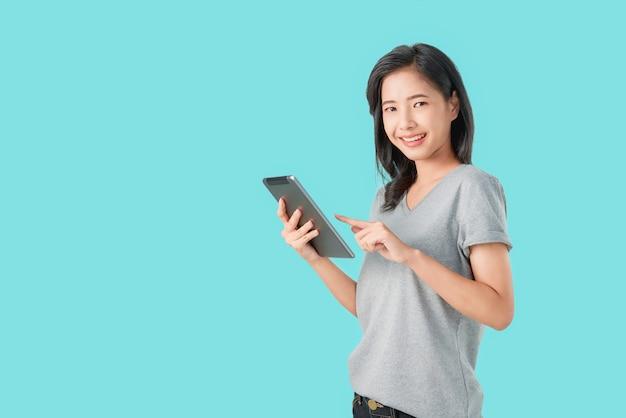 Lächelnde asiatin der junge, die digitale tablette mit dem zeigen des fingers auf hellblauem hintergrund hält.