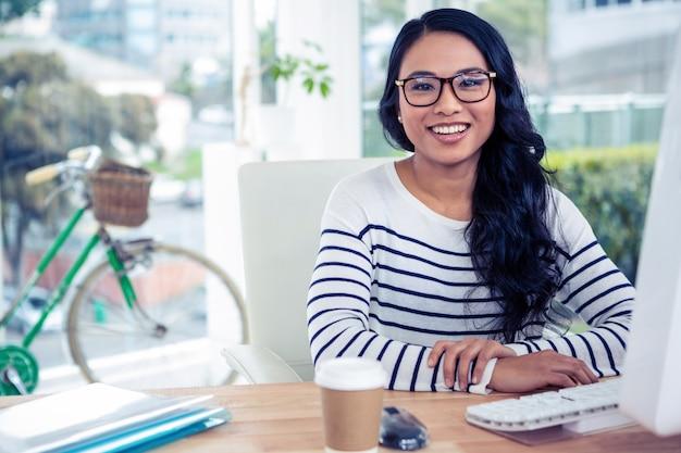 Lächelnde asiatin, die am schreibtisch aufwirft für kamera im büro sitzt