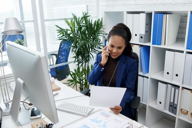 Lächelnde asiatin, die am schreibtisch im büro sitzt, dokument betrachtet und am handy spricht