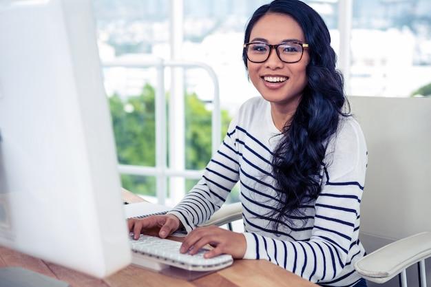 Lächelnde asiatin, die computer verwendet und die kamera im büro betrachtet