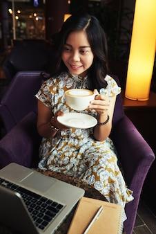 Lächelnde asiatin, die im café sitzt, schale cappuccino hält und laptopschirm betrachtet