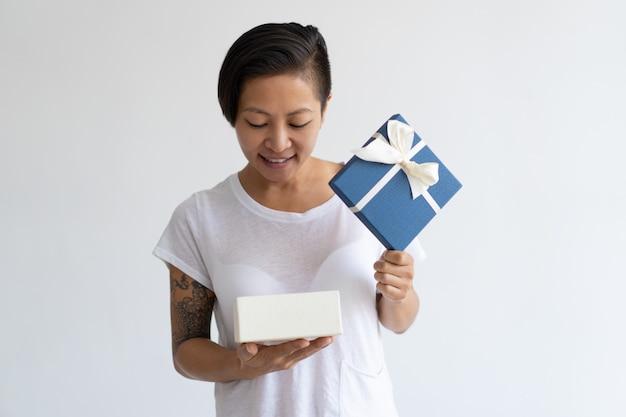 Lächelnde asiatin, die offene geschenkbox untersucht
