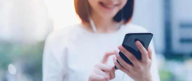 Lächelnde asiatin, die smartphone mit dem hören musik verwendet und im bürogebäude steht