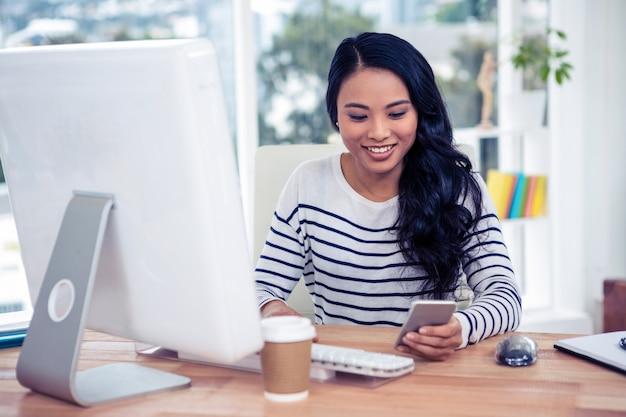 Lächelnde asiatin, die smartphone und computer im büro verwendet