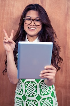 Lächelnde asiatin, die tablette hält und friedenszeichen mit der hand gegen hölzerne wand macht