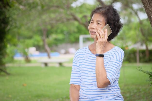 Lächelnde asiatische ältere frau, die den smartphone sitzt am garten verwendet