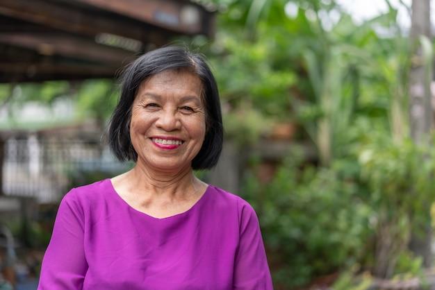 Lächelnde asiatische ältere frau, die draußen zu hause schaut und aufwirft