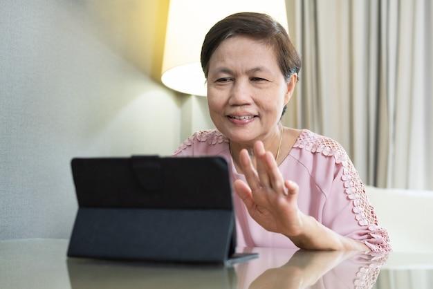 Lächelnde asiatische ältere frau, die videoanruf auf digitalem tablett während der quarantäne macht und zu hause isoliert.