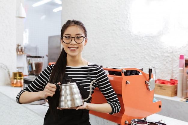 Lächelnde asiatische bardame mit wasserkocher