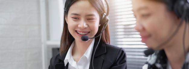 Lächelnde asiatische beraterin, die mikrofon-headset des kundenbetreuungs-telefonisten am arbeitsplatz trägt.