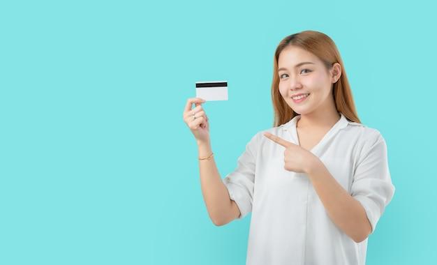 Lächelnde asiatische frau der junge, die fingerkreditkartenfreien raum zeigt