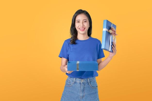 Lächelnde asiatische frau der junge in der blauen t-shirt holding und im offenen blauen geschenk