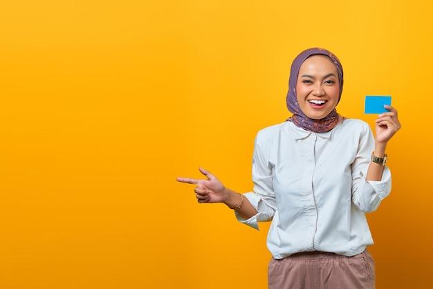 Lächelnde asiatische frau, die auf leerzeichen zeigt und eine leere karte auf gelbem hintergrund hält