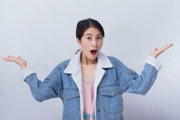 Lächelnde asiatische frau, die auf weiß mit exemplarplatz glücklich sich fühlt