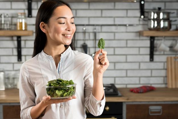 Lächelnde asiatische frau, die basilikumblatt in der küche betrachtet