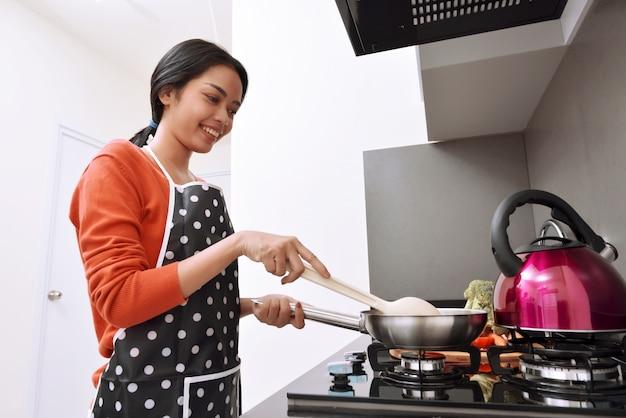Lächelnde asiatische frau, die bratpfanne und das kochen verwendet