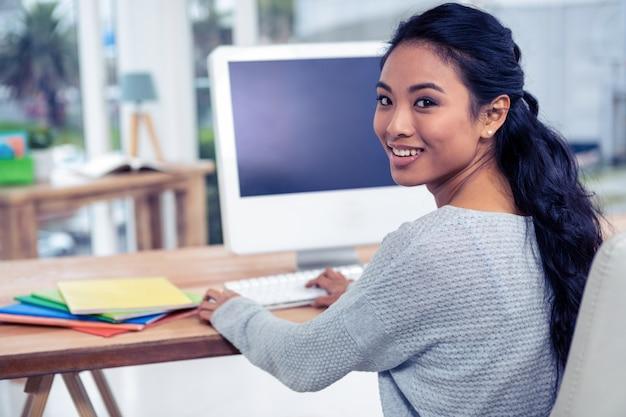 Lächelnde asiatische frau, die computer verwendet