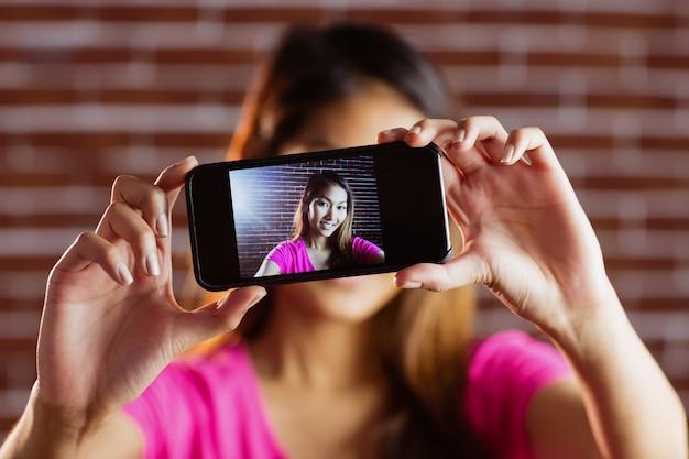 Lächelnde asiatische frau, die foto mit kamera auf backsteinmauer macht