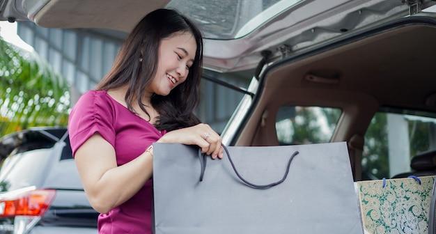 Lächelnde asiatische frau, die ihre einkaufstaschen in den kofferraum des autos steckt