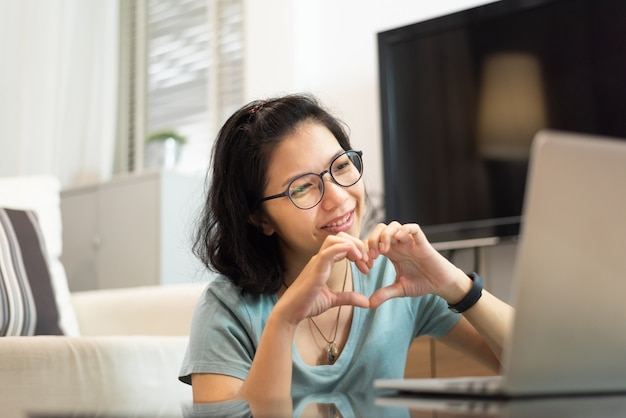 Lächelnde asiatische frau, die ihre hände in herzform während videoanruf mit laptop macht