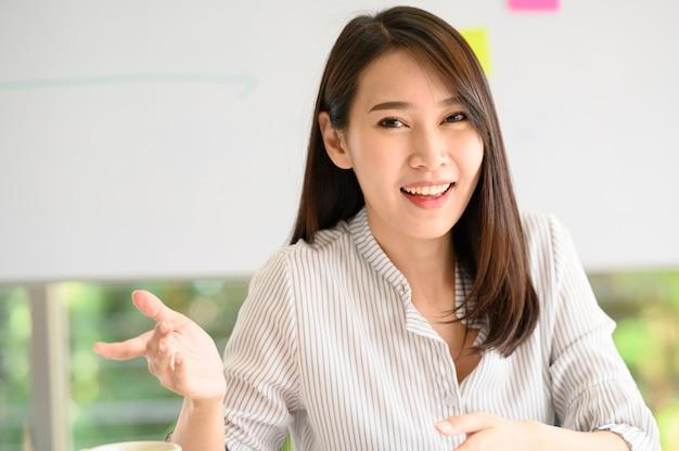 Lächelnde asiatische frau, die kamera etwas erklärt