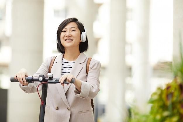 Lächelnde asiatische frau, die roller reitet