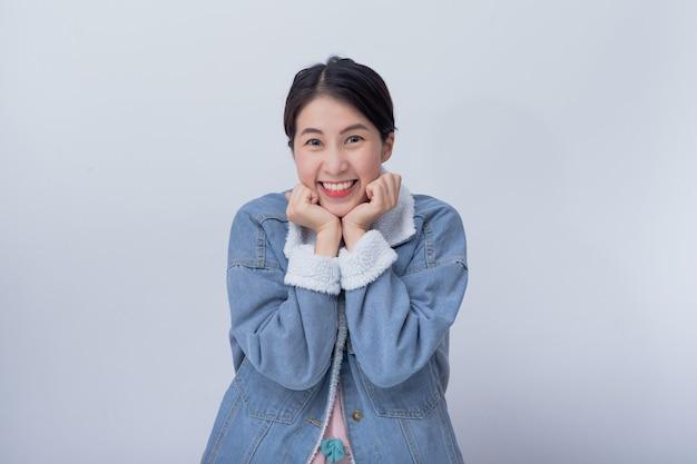 Lächelnde asiatische frau, die sich auf weißem hintergrund mit kopienraum glücklich fühlt