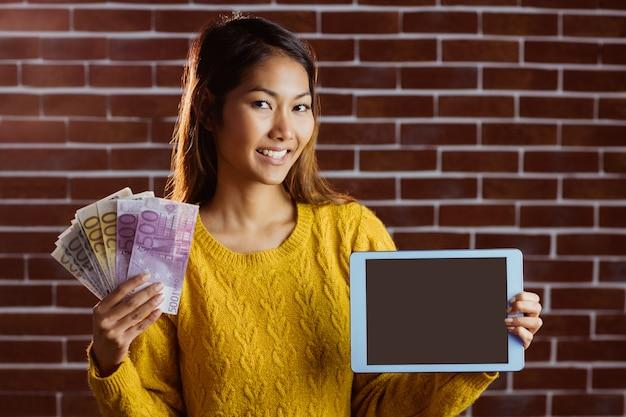 Lächelnde asiatische frau, die tablette und banknoten auf backsteinmauer zeigt