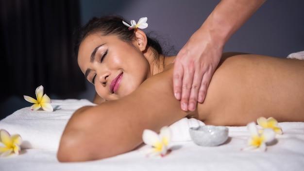 Lächelnde asiatische frau entspannen sich mit thai-öl-massage auf dem bett im spa-salon. körperpflegebehandlung
