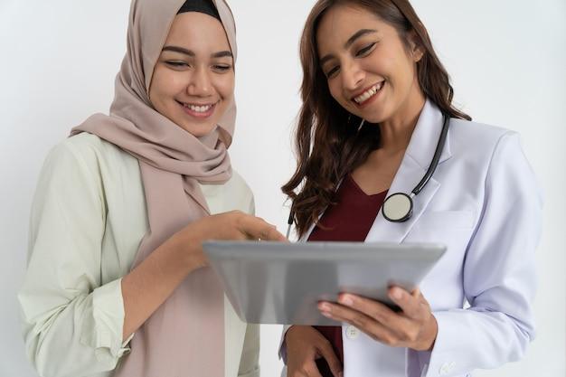 Lächelnde asiatische frau im kopftuch mit den händen, die auf den tablet-bildschirm zeigen und die glückliche schöne doktor...