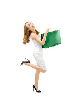 Lächelnde asiatische frau im weißen kleid, das grüne papiertüte hält