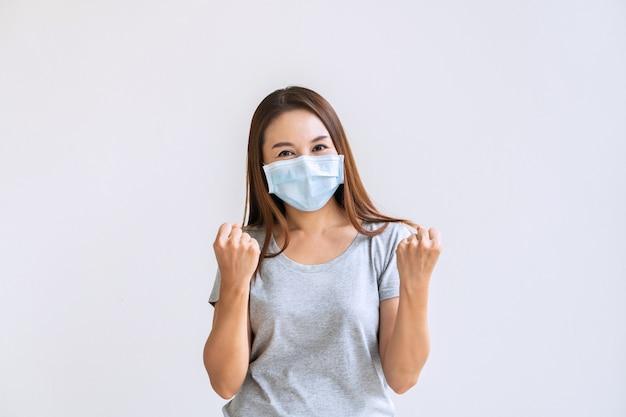 Lächelnde asiatische frau in der schützenden gesichtsmaske auf weißer wand, die hände in den fäusten erhebt und mit glück schreit.