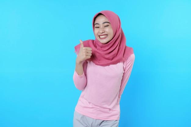 Lächelnde asiatische frau mit daumen auf hellblauem hintergrund isoliert mit hijab mit rosa t-shirt