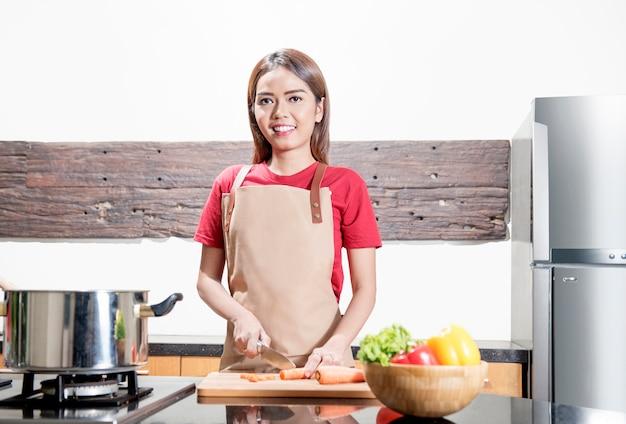 Lächelnde asiatische frau mit dem messer, welches das gemüse schneidet