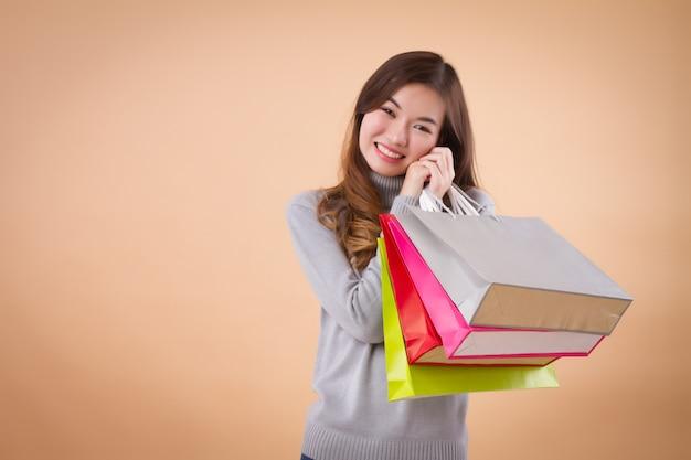 Lächelnde asiatische frau mit einkaufstüten