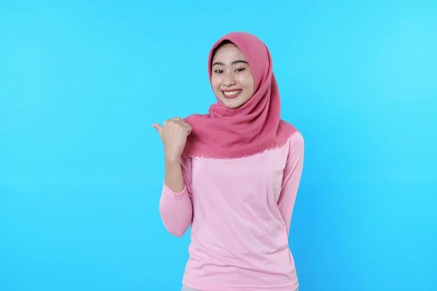 Lächelnde asiatische frau mit ihrem daumen zeigt isoliert auf hellblauem hintergrund und trägt hijab mit rosa t-shirt