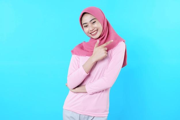Lächelnde asiatische frau mit ihrem fingerzeig isoliert auf hellblauem hintergrund trägt hijab mit rosa t-shirt