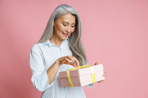 Lächelnde asiatische frau mittleren alters öffnet geschenkbox mit band auf rosa hintergrund