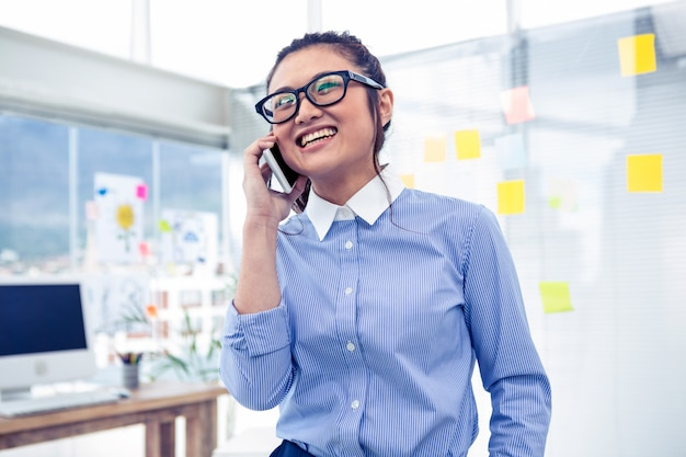 Lächelnde asiatische geschäftsfrau beim telefonanruf im büro