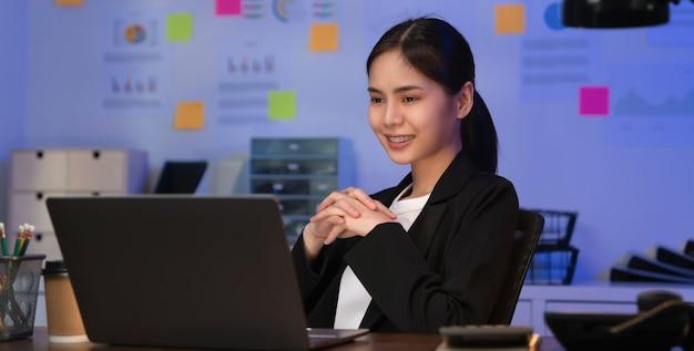 Lächelnde asiatische geschäftsfrau, die auf dem tisch sitzt und auf laptop-bildschirm auf dem büro in der nacht schaut.