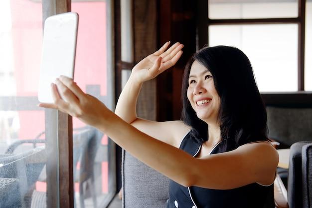 Lächelnde asiatische geschäftsfrau ist videoanrufe in sozialen medien mit tablet im café. sie spricht während der covid-19-epidemie für arbeit und technologie am arbeitsplatz im büro oder arbeitet von zu hause aus