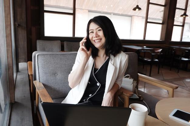Lächelnde asiatische geschäftsfrau ruft mit smartphone online an, arbeitet in sozialen medien am arbeitsplatz im modernen büro oder entspannt sich im café. lebensstil von menschen mit technologiekonzept.