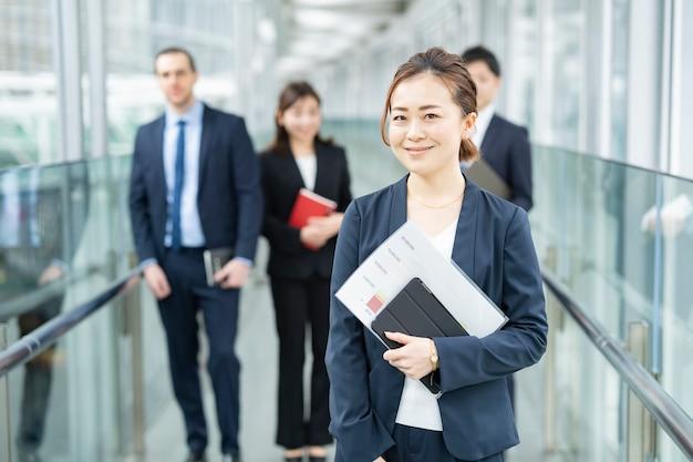 Lächelnde asiatische geschäftsfrau stehend und ihr geschäftsteam
