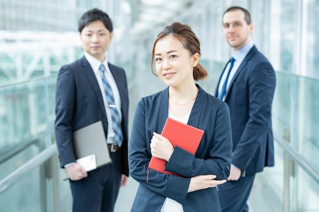 Lächelnde asiatische geschäftsfrau und ihr geschäftsteam