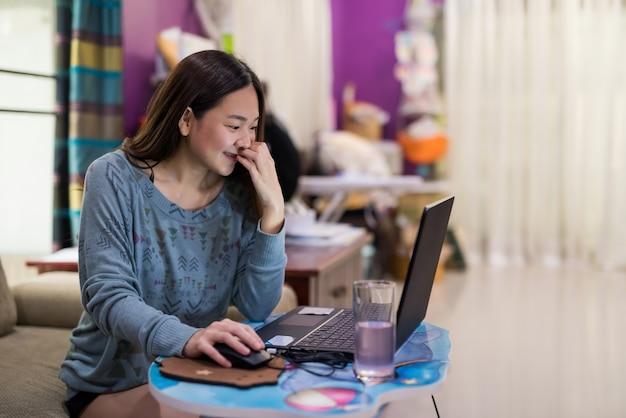 Lächelnde asiatische junge frau arbeitet von zu hause aus per videoanruf mit familie oder freunden per computeranwendung. sie bleibt zu hause sicher, um eine covid-19-delta-pandemie zu verhindern.