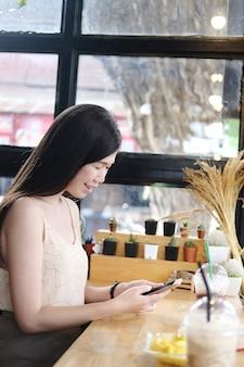 Lächelnde asiatische junge geschäftsfrau ist online-shopping und entspannt sich mit smartphone im café