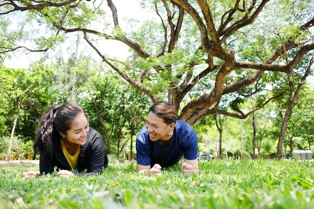 Lächelnde asiatische junge paare lieben es, zusammen auf der wiese im garten zu trainieren und zu trainieren.