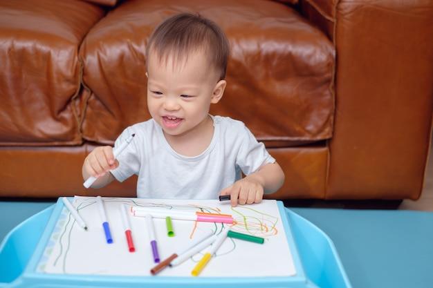 Lächelnde asiatische kleinkindjungenzeichnung, kritzelnd mit buntem hersteller